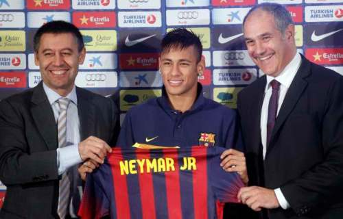Neymar poses with his new jersey next to sports director Andoni Zubizarreta and vice-president Ferran Bartomeu after signing a five-year contract in Barcelona